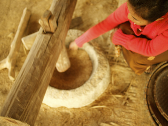A woman moves rice grains to help them become husked