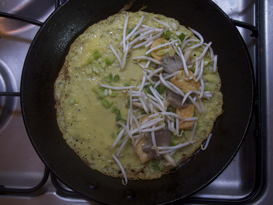 Banh xeo in a frying pan beginning to cook