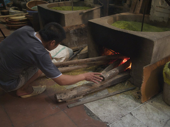 Adjusting the fire during the roasting of young green rice