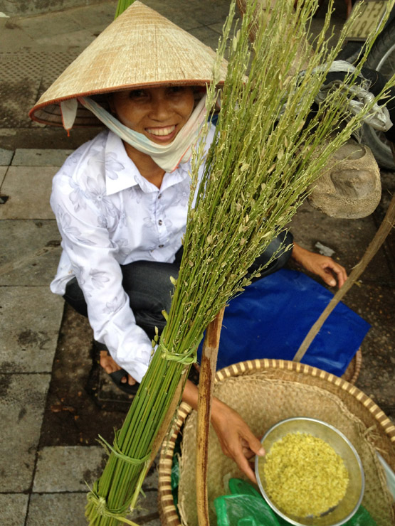 A street vendor with young green rice, com, for sale
