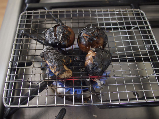 Charred shallots and ginger on a gas stove