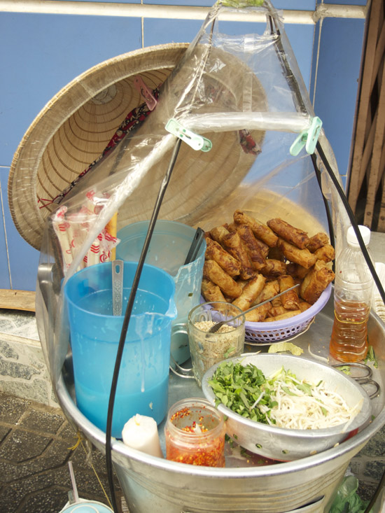 Vegetarian mobile food vendor's ingredients for fresh noodle bowl with spring rolls and thin rice crepes (bánh cuốn).